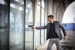 Stock Photo of Young detective or policeman or mobster firing a gun to a window glass