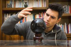 Young man predicting the future by looking into crystal ball Stock Photos