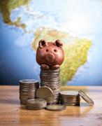 brown piggy bank and coins - stock photo