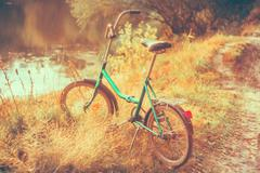 Little green bicycle standing on yellow autumn meadow - stock photo