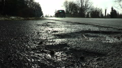 Bad road conditions, broken asphalt, passing cars Stock Footage