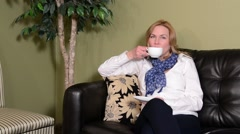 Woman drinking coffee in a reception area Stock Footage