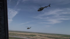 Kiowa and Huey gunship fly in formation Stock Footage