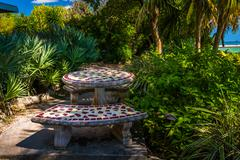 Benches and table in a garden in key west, florida. Stock Photos
