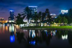 Buildings and palm trees reflecting in lake eola at night, orlando, florida. Kuvituskuvat