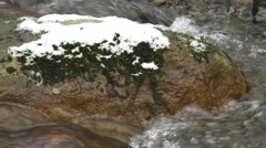 Winter stream flowing fast around snow covered boulder Stock Footage