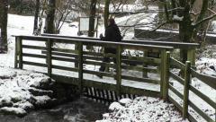 Female hiker walks across wooden footbridge in winter snow Stock Footage