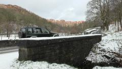 4x4 Cars drive in winter snow over a stone bridge Stock Footage