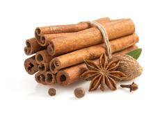 Cinnamon sticks, anise star and spices on white Stock Photos