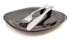 knife and fork at plate on white - stock photo