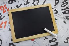 Slate board on calendar sheets with chalk Kuvituskuvat