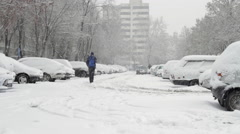 Young Man Walking In A Parking Lot Covered In Snow, Blizzard, Winter, Tilt Down Stock Footage