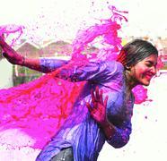 Splash of wet colors on female during holi celebration in india. Stock Photos
