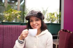 Cute smiling woman drinking a coffee sitting inside in cafe restaurant.. Kuvituskuvat