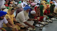 Poor people eating free food at a soup kitchen in Golden Temple. Amritsar, India Stock Footage