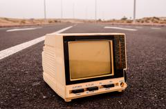 television abandoned on the road - stock photo