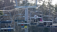 Downhill Skiers On A Quad Chairlift Stock Footage