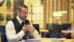 Businessman having a telephone conversation with earphones in cafe by window HD Stock Footage