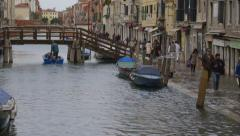 Boat passes under low bridge during flooding in Venice Stock Footage
