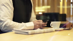 Businessman hands sending sms, texting on smartphone sitting in cafe HD - stock footage