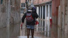 Flooded street, venice, italy - man carries girl Stock Footage