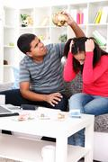 frustrated couple doing their bills in the living-room - stock photo