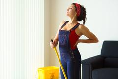 Portrait woman doing chores cleaning floor with backache Stock Photos
