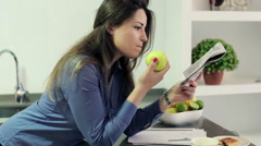 Businesswoman reading newspaper, eating green apple in kitchen at home HD Stock Footage