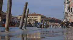 A flooded venice footpath due to sea level rise as boat passes Stock Footage