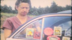 1582 - grandma puts a travel sticker on the car window - vintage film home movie - stock footage