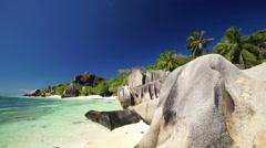 huge granite rocks on sandy beach - stock footage