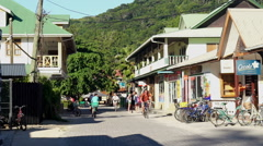Tourists on bikes in tropical island village Stock Footage
