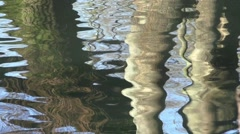 reflections of tree trunks a rippling water - stock footage