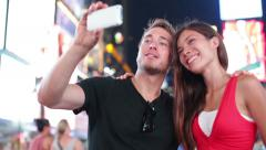 Dating young couple taking selfie  self-portrait photo on Times Square, New York Stock Footage