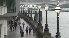 People walking along the riverside in London Stock Footage