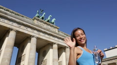 Woman waving hand saying hello running in Berlin Germany by Brandenburg Gate Stock Footage