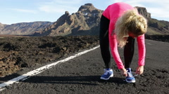 Athlete runner woman tying running shoes on jogging run outdoors on road Stock Footage
