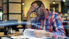Sad, unhappy man reading documents, bills sitting in cafe HD Stock Footage