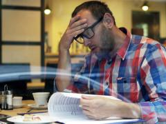 Sad, unhappy man reading documents, bills sitting in cafe NTSC Stock Footage