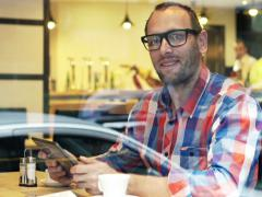 Portrait of happy man with tablet computer sitting in cafe NTSC Stock Footage