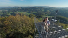 beutiful couple on to of a lookout tower in the middle of a nice landscape - stock footage