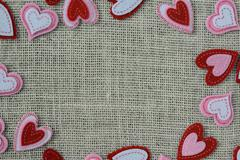 red hearts frame or border on burlap background - stock photo