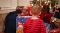 Little boy looking at christmas presents Stock Footage