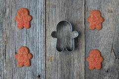 gingerbread men and cookie cutter on wood background - stock photo