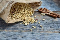 Granola in burlap sack  spilling onto wooden background Stock Photos