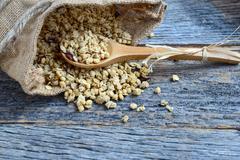 granola in burlap sack  spilling onto wooden background - stock photo