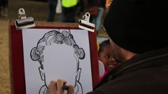 Artist drawing mouth of little girl on caricature Stock Footage
