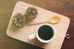 black coffee and spoon on wooden tray with pine cone, retro filter effect - stock photo