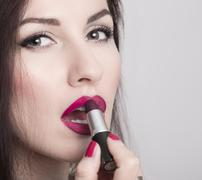 Close-up of woman applying lipstick. Model looks like Monica Bellucci - stock photo