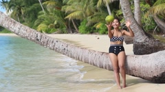 Woman in a retro swimsuit throws on the beach with coconut Stock Footage
